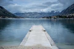 石码头在亚得里亚海的海湾山背景中 免版税库存照片