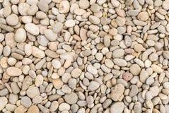 石米黄光滑的河小卵石岸 库存图片