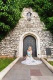 石老墙壁的背景的年轻美丽的妇女有一个小葡萄酒门的纠缠了与常春藤 库存图片