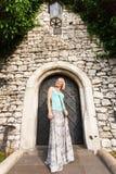 石老墙壁的背景的年轻美丽的妇女有一个小葡萄酒门的纠缠了与常春藤 免版税库存图片