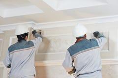 石膏工在室内墙壁工作 免版税库存照片
