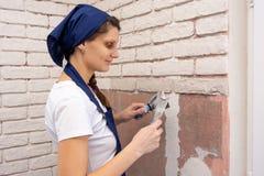 石膏工女孩涂灰泥墙壁,计划仿制砖砌 库存图片
