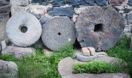 石花岗岩转动与在绿草隔绝的生锈的金属外缘在墙壁附近 库存照片