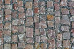 石花岗岩铺有鹅卵石的路面背景或纹理 老鹅卵石路面特写镜头抽象背景在布拉格 免版税库存照片