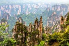 石英岩砂岩柱子和峰顶与绿色树和登上 免版税库存图片