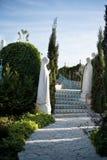 石走道 妻子老雕象,妇女,玛丽周围 胡同在有花和树的美丽的庭院里 在的夏天 库存照片