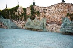 石走道 胡同在有石长凳、阶梯步级、花和树的美丽的庭院里 夏天在庭院里 免版税库存照片