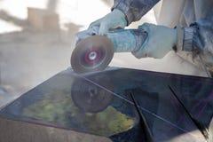 石雕刻家飞白岩花岗岩的工作 由磨床的石切口 多灰尘的工作 免版税库存照片
