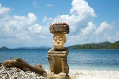 石雕刻的人坐在印度尼西亚的高旅游季节的海滩 免版税库存照片