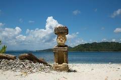 石雕刻的人坐在印度尼西亚的高旅游季节的海滩 免版税库存图片