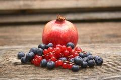 石榴、蓝色莓果和红浆果在木背景 库存图片