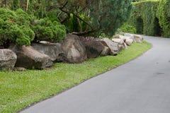 石头和植物在走道旁边装饰在公园 图库摄影