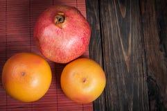 石榴和葡萄柚 新鲜水果 在木头的水果品种 背景许多饺子的食物非常肉 免版税图库摄影