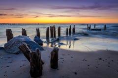 石头和防堤在日落 免版税库存图片