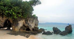 石洞穴和绿色树在蓝色海。 库存照片