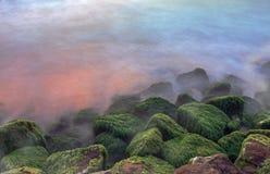 石头在日落期间的海洋 库存照片