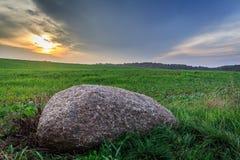 石头在日落期间的草甸 免版税库存图片