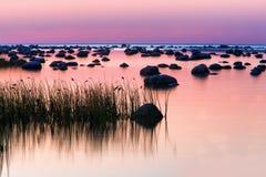 石头在日落紫色的海 免版税库存图片