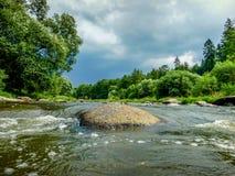石头在有一个黑暗的天空和森林的河 库存照片