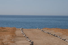 石头在海滩的被排行的道路 免版税库存照片