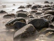 石头在长的曝光的被弄脏的水中 免版税库存图片