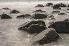 石头在长的曝光的被弄脏的水中 库存图片