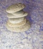 石头塔在发光的蓝色盐背景的  免版税库存照片