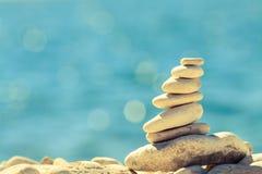石头平衡在海滩,在蓝色海的堆 库存照片
