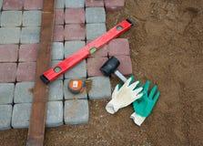 石头阻拦橡胶锤子水平手套和卷尺 免版税库存图片