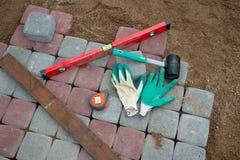 石头阻拦橡胶锤子水平手套和卷尺 图库摄影