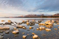石头由太阳在日落,湖Tekapo,新西兰点燃了 库存图片