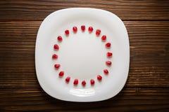 石榴种子以圈子的形式在白色板材的 库存图片