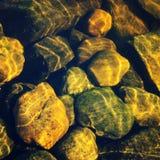 石头通过水 表面上的波纹 免版税库存图片