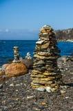 石头金字塔在海滩的在晴天 库存图片