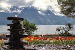 石头,郁金香临近湖和山 免版税库存照片