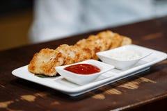 矿块用蕃茄和酸性稀奶油调味汁在一块白色板材在一块灰色餐巾以一张木桌为背景 免版税库存图片