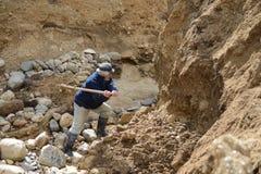 矿工开采金子在地球边缘 免版税库存照片