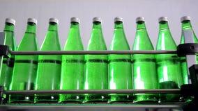 矿泉水的绿色瓶移动沿着自动生产线 影视素材