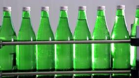 矿泉水的绿色瓶移动沿着自动生产线 股票录像