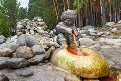 矿物来源水 从男孩图的形式的水流量有水罐的 Arshan 俄国 库存照片
