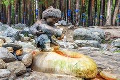 矿物来源水 从男孩图的形式的水流量有水罐的 Arshan 俄国 免版税库存照片