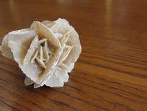 矿物沙漠在木桌上上升了 亦称沙子上升了或玫瑰色玫瑰色玫瑰色的岩石或的亚硒酸盐或的石膏或baryte上升了 库存照片