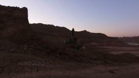 矿物的提取在上面曝露的猎物的 Eksakvator装载岩石入卡车 晚上摄影 移动录影操作员forw 影视素材