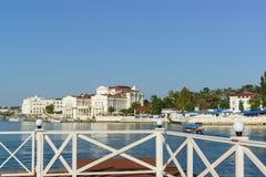 码头的在火炮的栏杆小船的和轮渡咆哮 海边镇的白色建筑学 图库摄影
