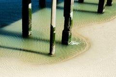 码头的柱子由低潮的 免版税库存图片