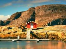 码头的,岩质岛,挪威红色船库 在码头的传统红色白色大厦接近海 免版税库存照片
