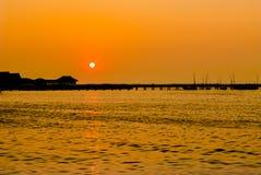 码头和海剪影的在日落 免版税库存图片