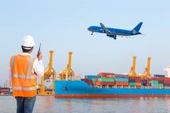码头工人谈话在控制装货的携带无线电话 免版税库存照片