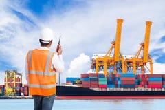 码头工人谈话在控制装货的携带无线电话 库存图片