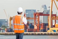 码头工人谈话在控制装货的携带无线电话 库存照片